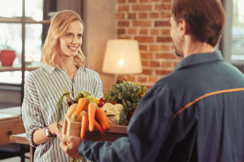 Pretty blonde receiving organic vegetables. Home delivery. Positive delighted female keeping smile on her face and stretching hands while taking package royalty free stock photos