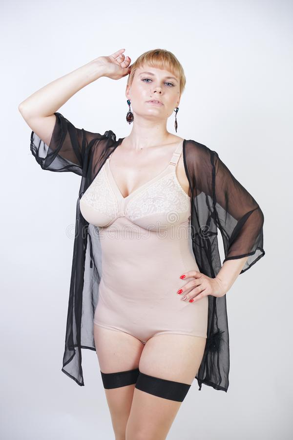 Pretty blonde short hair retro woman with curvy body posing in beige vintage bodysuit and sexy classic stockings with seam on whit royalty free stock images