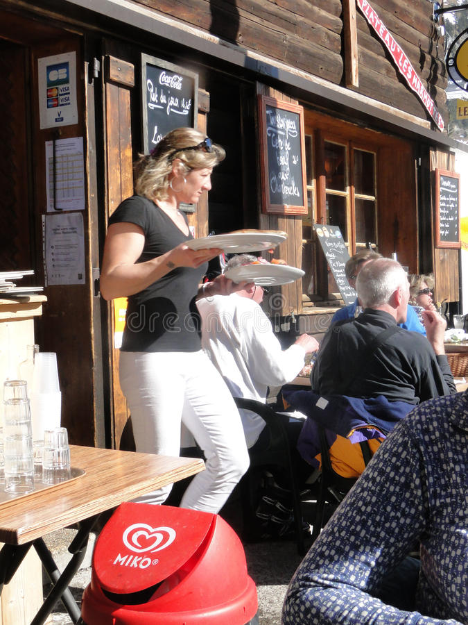 A pretty blonde waitress serves lunch outdoors