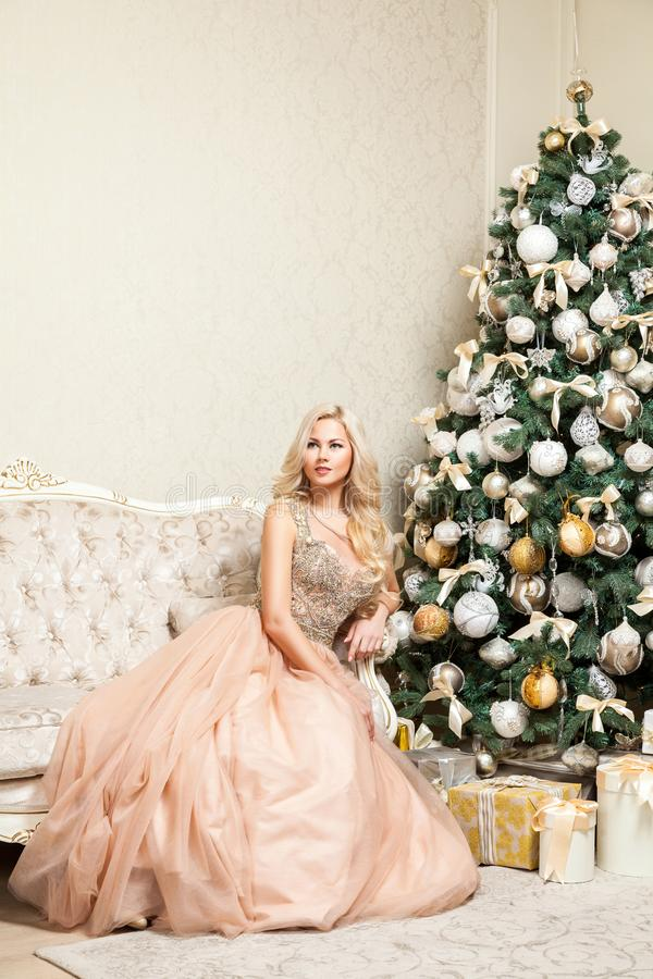 Pretty blonde woman in beautiful holiday puffy elegant evening dress with makeup and curly hairstyle sitting posing on sofa near royalty free stock images