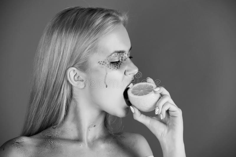 Pretty blonde woman with creative fashionable makeup bite lemon, vitamin. Pretty blonde woman with creative fashionable makeup on face hold and bite lemon fruit royalty free stock image