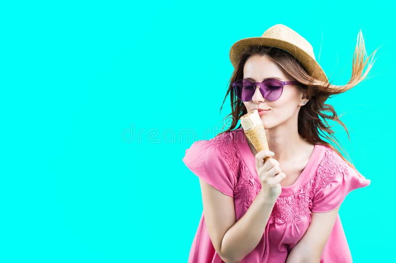 Girl with Icecream. Pretty blonde woman dressed in rose shirt, hat and sunglasses eating wafle icecream before blue background stock photos