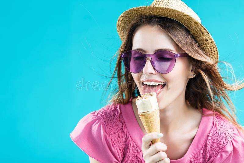Girl with Icecream. Pretty blonde woman dressed in rose shirt, hat and sunglasses lick icecream before blue background stock images