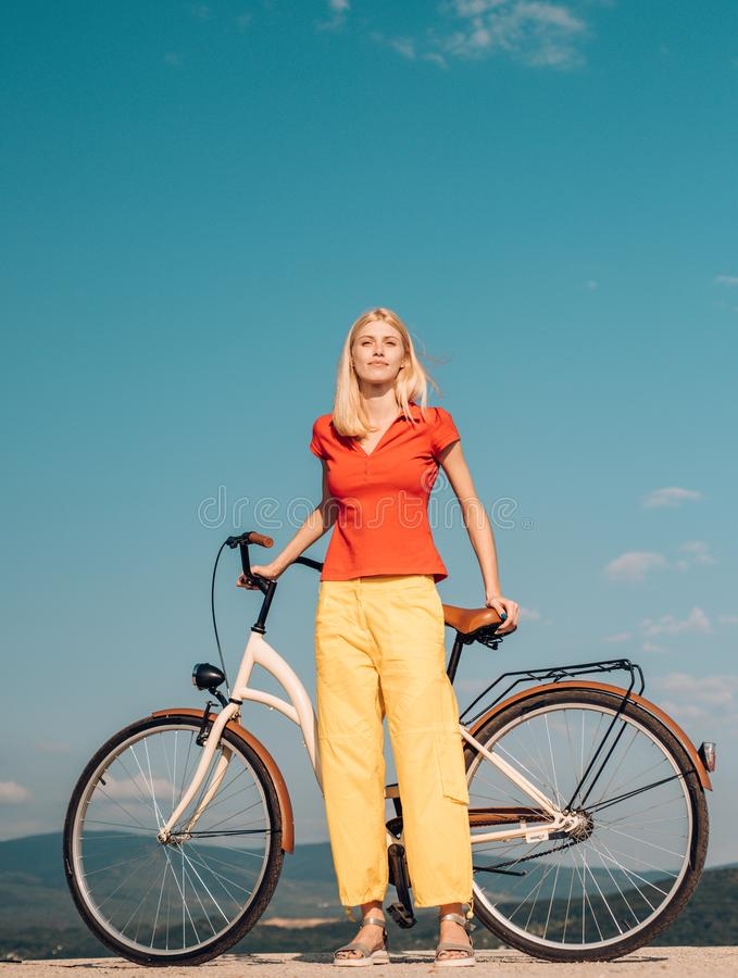 Pretty blonde woman enjoy her walk with bike. Cycling concept. Beautiful woman took a break while riding her vintage stock photos