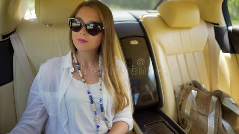 Pretty blonde woman enjoying trip on backseat of luxury limousine, tourism royalty free stock photography