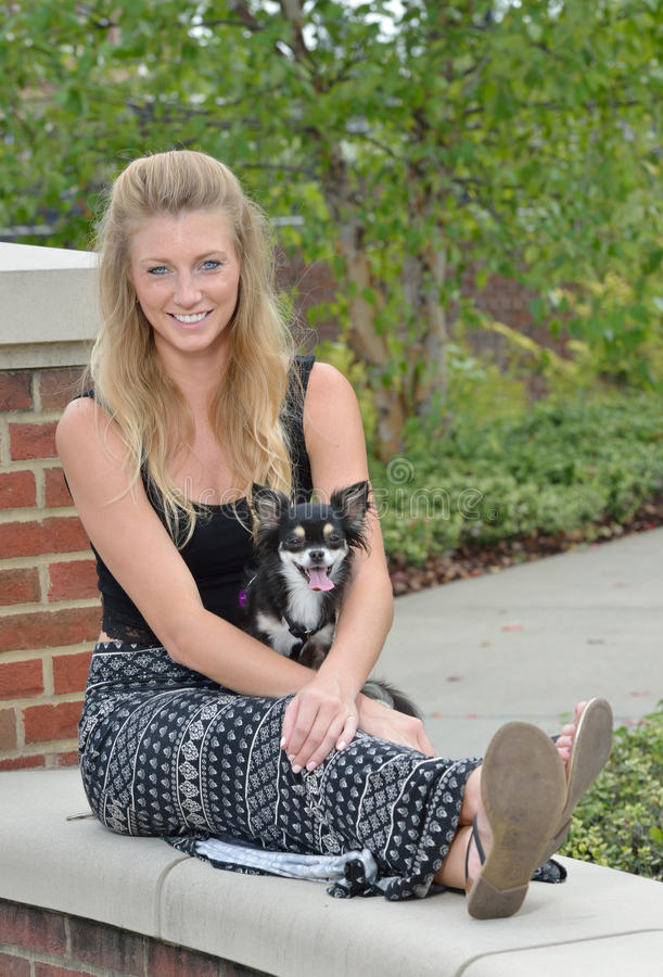 Pretty blonde woman with her pet Chihuahua. Stunning young blonde woman in a patterned long skirt and black top sits with her pet Chihuahua royalty free stock photo