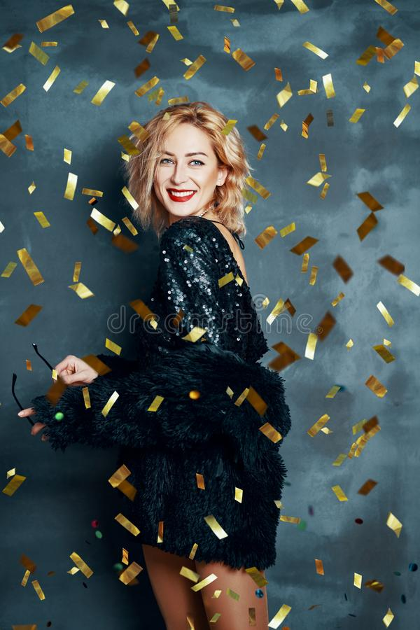 Pretty blonde woman in little black dress dancing on confetti royalty free stock images