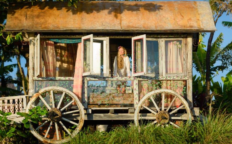 Pretty blonde woman and antique gypsy caravan 4. Pretty blonde woman looking out of the window of an antique gypsy caravan at sunset royalty free stock photo
