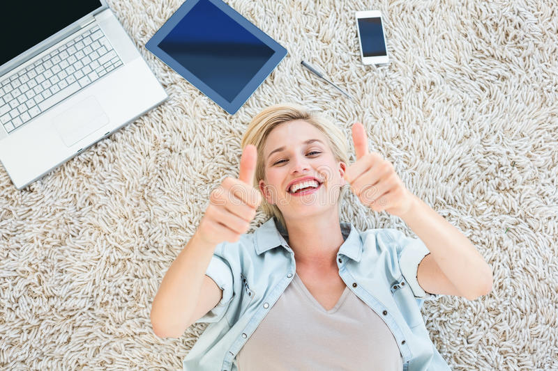 Pretty blonde woman lying on the floor and smiling at the camera thumbs up stock photos