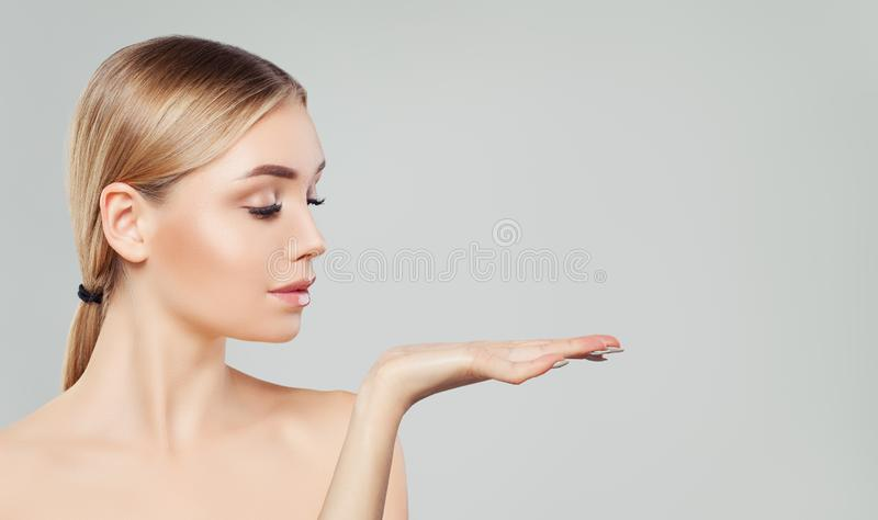 Pretty blonde woman showing her empty open hand with copy space for advertising marketing or product placement. Beauty girl stock image