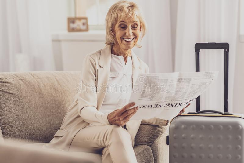 Pretty blonde woman sitting near her luggage. Ready for trip. Charming businesswoman expressing positivity while reading news royalty free stock photography