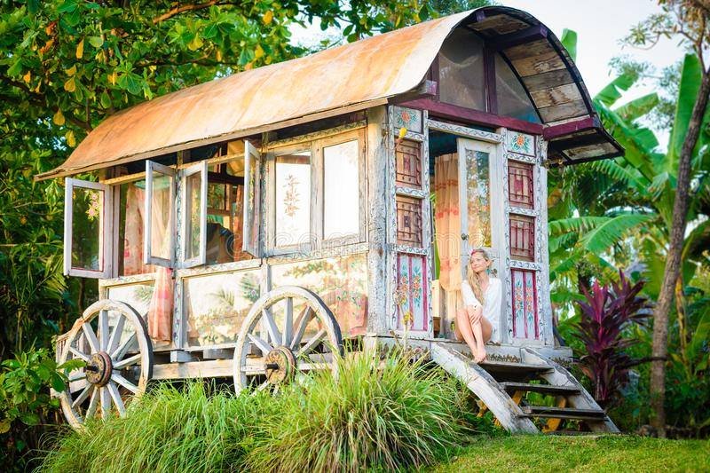 Pretty blonde woman and antique gypsy caravan 8 stock photography