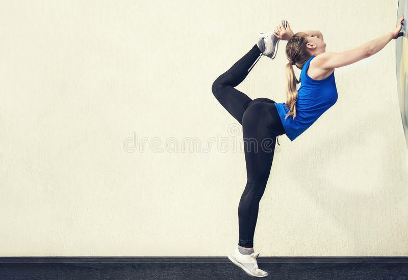 Pretty blonde woman with slim body stand in yoga pose with one leg raised up. Gymnastic pose vertical. stock photography