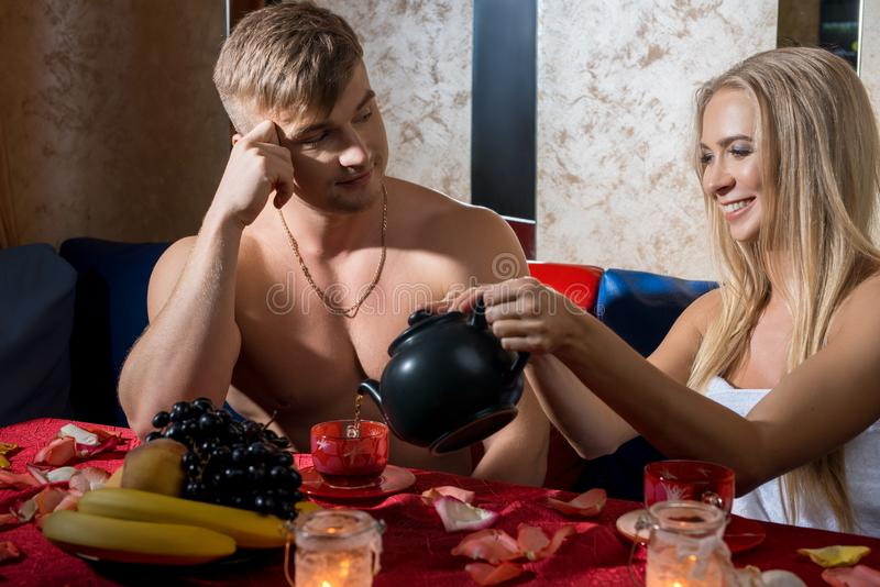 Young couple drinking tea together in sauna royalty free stock images