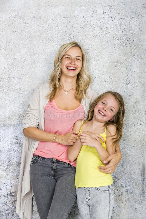Free Pretty, Blonde Young Mother Poses And Cuddles With Her Daughter In Front Of A Concrete Wall And Having A Lot Of Fun Royalty Free Stock Photos - 155112138