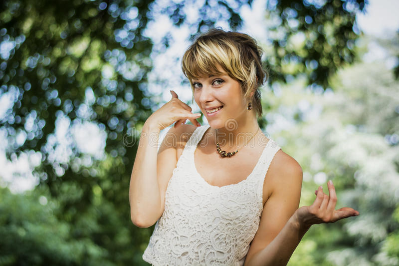 Pretty blonde young woman doing call me sign with royalty free stock photos