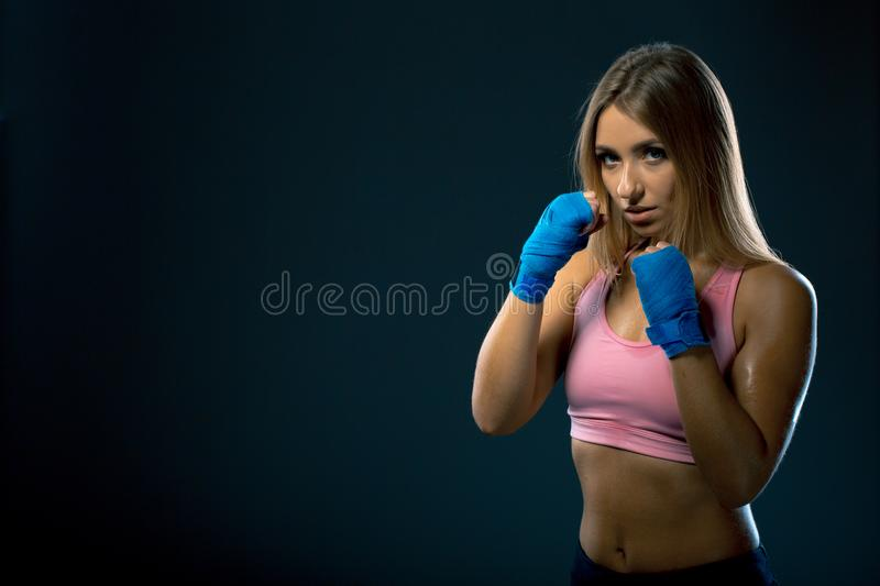 Pretty young woman posing in a boxing stand. Sweaty girl in boxing bandages after training on a dark background. Copy space royalty free stock photo