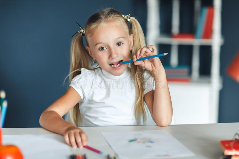 Pretty blondy girl thinking while doing her homework and holding a blue pencil, at home table. Education and school concept royalty free stock images