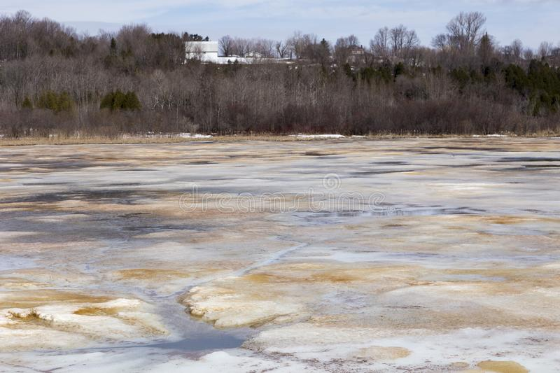 Pretty blue, brown and white colourful surface patches in the early spring thawing Léon-Provencher marsh stock images
