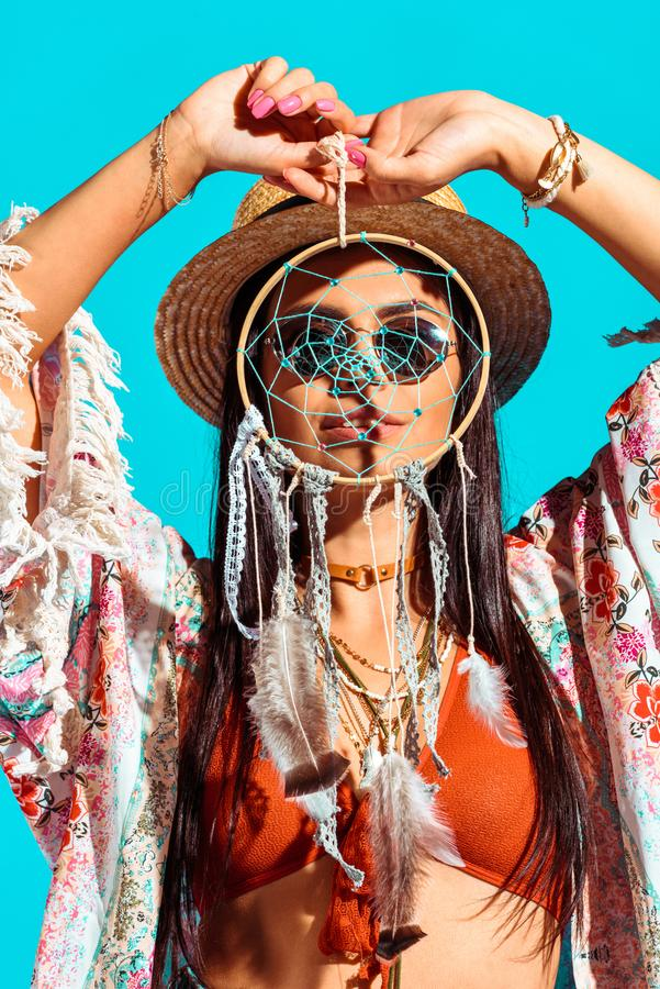 Pretty bohemian girl holding dreamcatcher in front of face. Isolated on turquoise stock photography