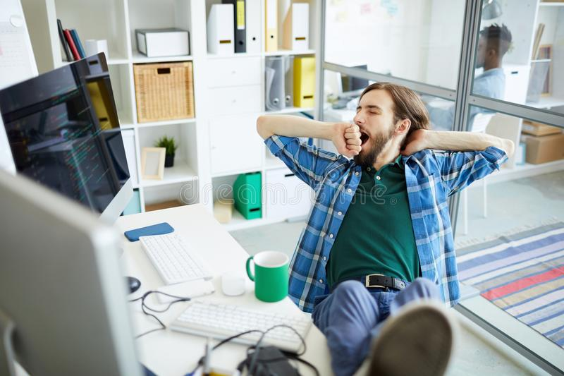 Pretty bored. Young tired or bored software developer sitting in front of computer monitor and yawning stock photography