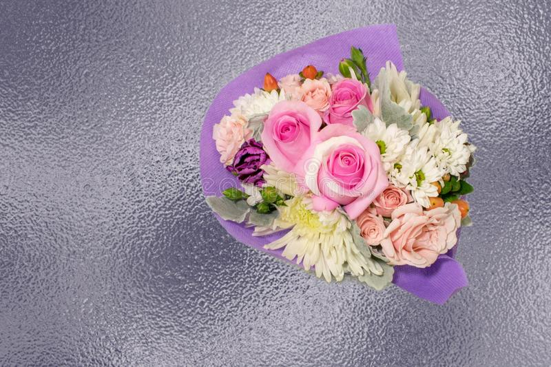 A miniature bouquet of roses on lavender foil background royalty free stock image