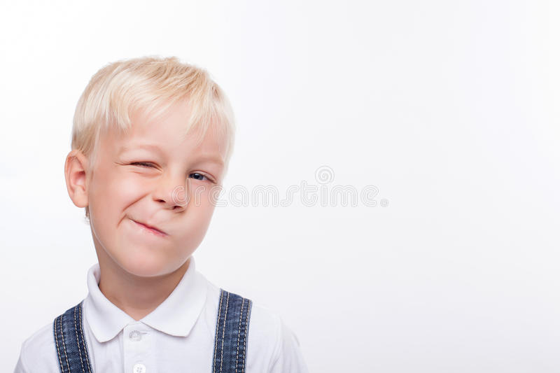 Pretty boy is making faces for fun. Cheerful male child is standing and grimacing. He is looking forward and winking. The schoolboy is smiling. Isolated and copy stock image