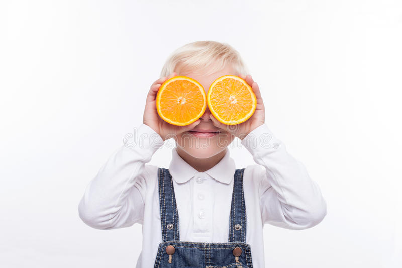 Pretty boy is playing with healthy fruit. Cheerful male child is holding two pieces of orange and covering his eyes with it. The schoolboy is standing and royalty free stock photo