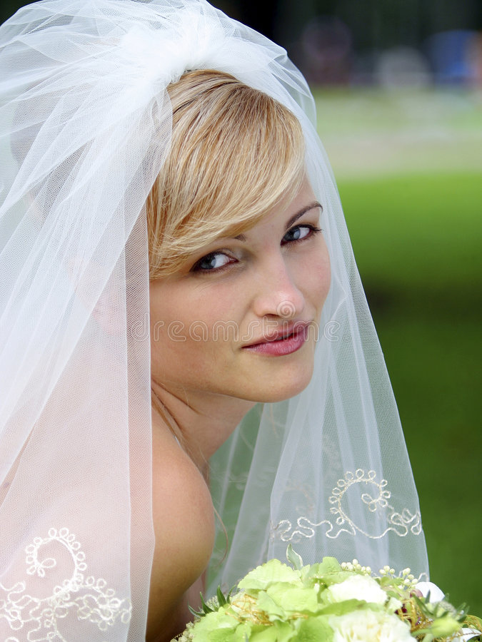 Pretty bride with bouquet. Portrait of pretty bride with bouquet and veil royalty free stock photo
