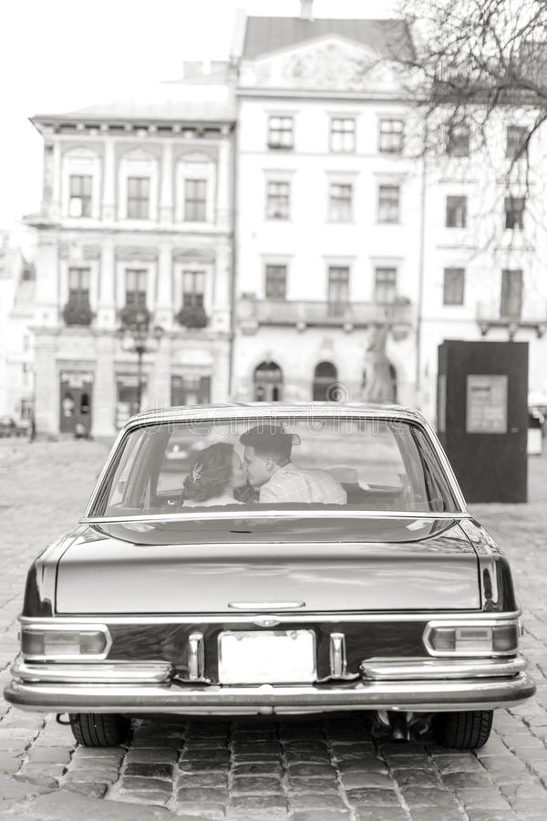 Pretty bride and handsome groom kissing and hugging in the retro car. Wedding day, retro style, old city center. Retro old car royalty free stock photo
