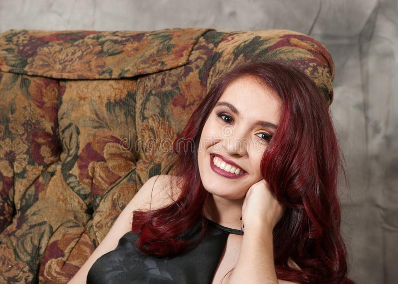 Pretty brown-eyed redhead girl reclining in chair stock photography