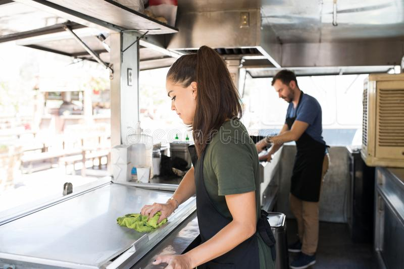 Woman cleaning a food truck royalty free stock photography