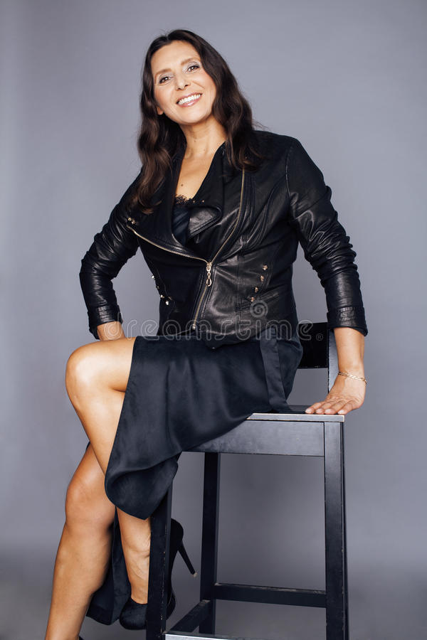 Pretty brunette confident stylish real mature woman sitting on chair in studio, on gray background wearing leather stock image