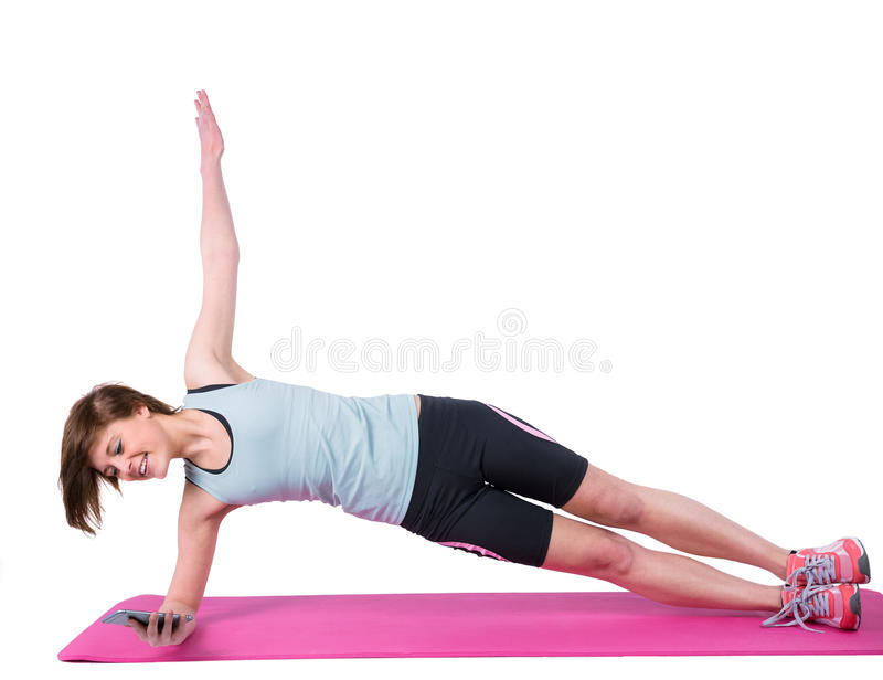 Pretty brunette doing side plank on exercise mat. On white background royalty free stock images