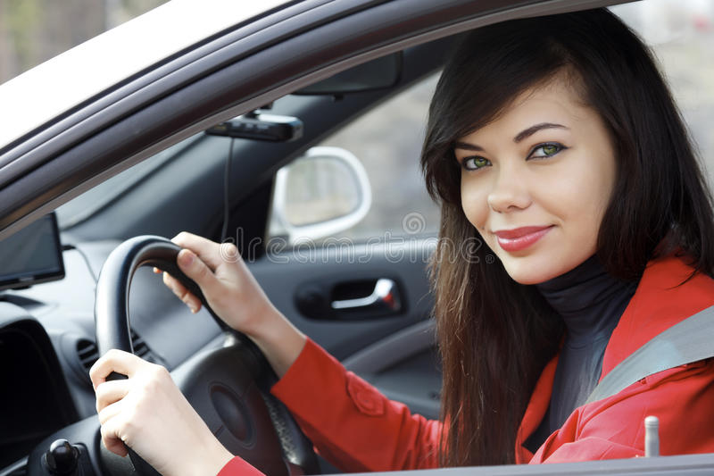 Pretty brunette driving a car royalty free stock image