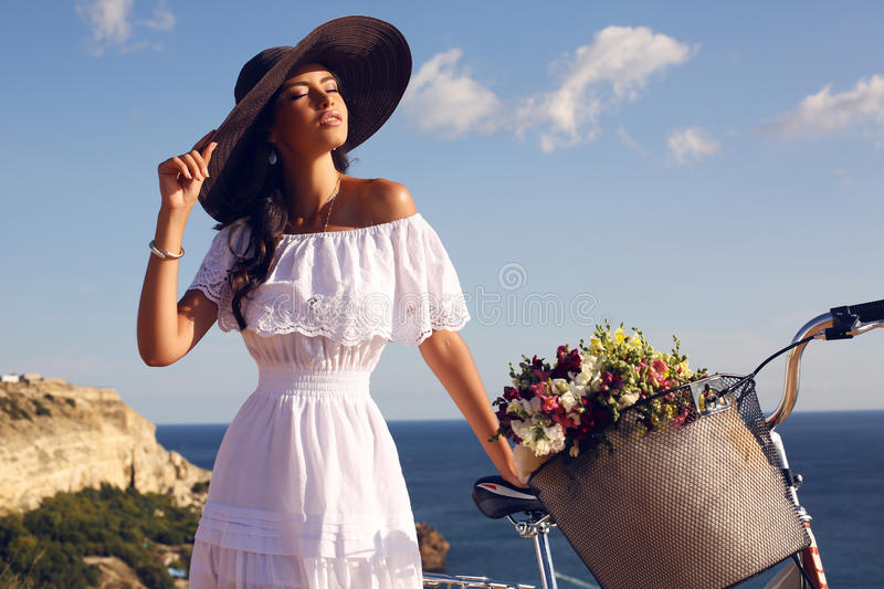 Pretty brunette in elegant dress and hat riding a bicycle along the coast. Fashion outdoor photo of beautiful girl with dark hair in elegant hat and white dress stock photos