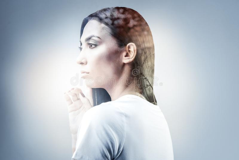 Pretty brunette girl being deep in thoughts. Need to concentrate. Attractive female standing in semi position and looking forward while raising right hand royalty free stock photo