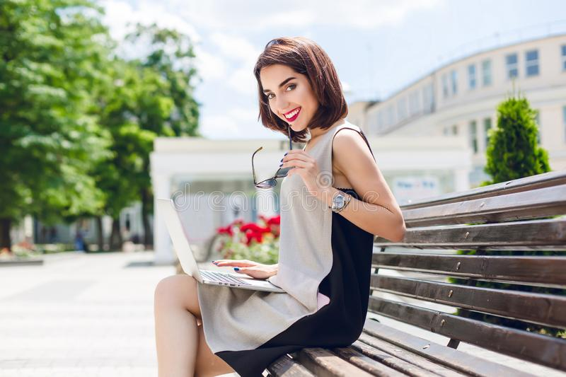 A pretty brunette girl in gray and black dress is sitting on the bench in city. She has a laptop on knees and smiling royalty free stock image