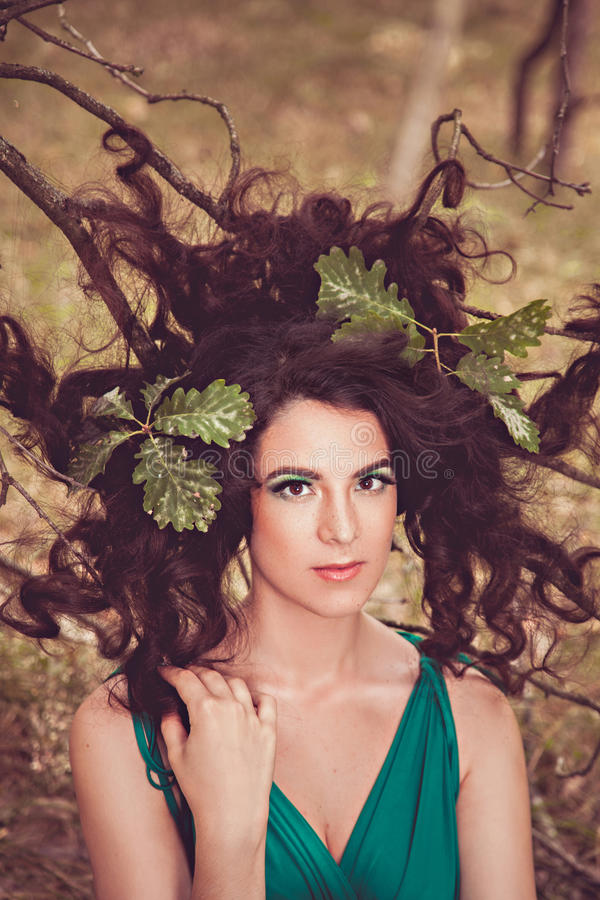 Pretty brunette girl with hair on the branches stock photography