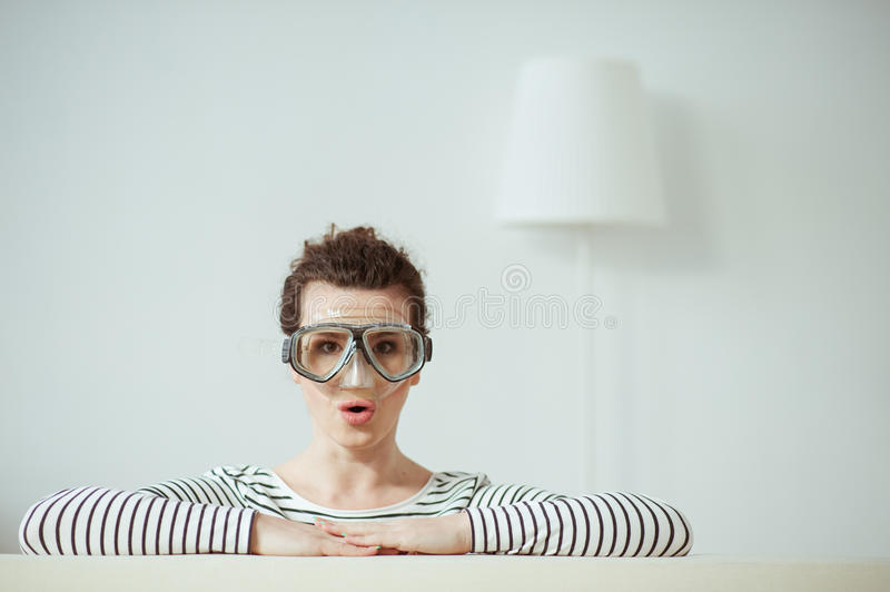 Pretty brunette girl is making fun in apartment stock image