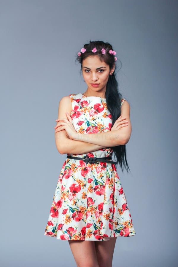 Pretty brunette girl posing. Brunette long hair girl posin in flower painted dress on grey background royalty free stock images
