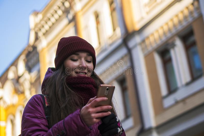 Pretty Brunette Girl Wearing Purple Winter Coat, Hat and Scarf, Walking by European Street at Winter, Using Her. Smartphone and Making Selfie. City Travel royalty free stock photo