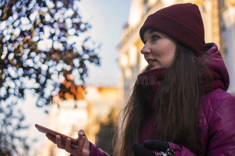 Pretty Brunette Girl Wearing Purple Winter Coat, Hat and Scarf, Walking by European Street at Winter, Using Her. Smartphone and Making Selfie. City Travel royalty free stock photography