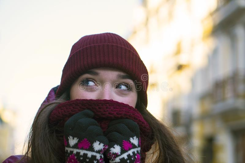 Pretty Brunette Girl Wearing Purple Winter Coat, Hat and Scarf, Walking by European Street at Winter, Wrapped up in a. Scarf. City Travel stock photo
