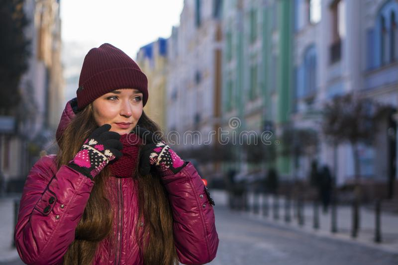 Pretty Brunette Girl Wearing Purple Winter Coat, Hat and Scarf, Walking by European Street at Winter, Wrapped up in a. Scarf. City Travel royalty free stock photography