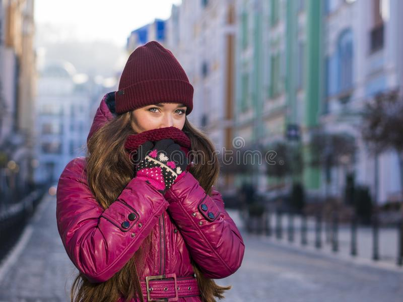 Pretty Brunette Girl Wearing Purple Winter Coat, Hat and Scarf, Walking by European Street at Winter, Wrapped up in a. Scarf. City Travel stock images