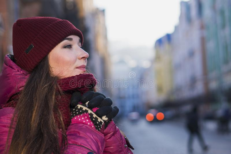 Pretty Brunette Girl Wearing Purple Winter Coat, Hat and Scarf, Walking by European Street at Winter, Wrapped up in a. Scarf. City Travel royalty free stock photos
