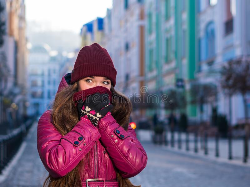 Pretty Brunette Girl Wearing Purple Winter Coat, Hat and Scarf, Walking by European Street at Winter, Wrapped up in a. Scarf. City Travel stock image