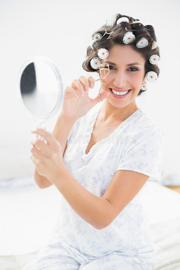 Pretty Brunette In Hair Rollers Holding Hand Mirror And Using Ey Stock Image