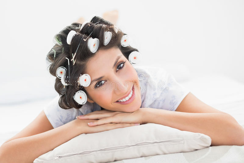 Pretty Brunette In Hair Rollers Lying On Her Bed Smiling At Camera Stock Images